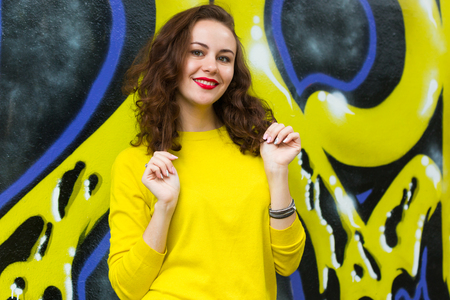 Portrait of cute girl in yellow pullover on graffiti wall background Фото со стока