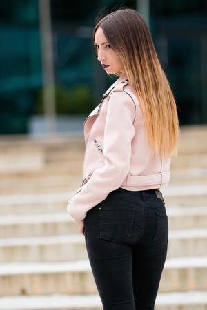 Portrait of informal fashionable girl on modern building background