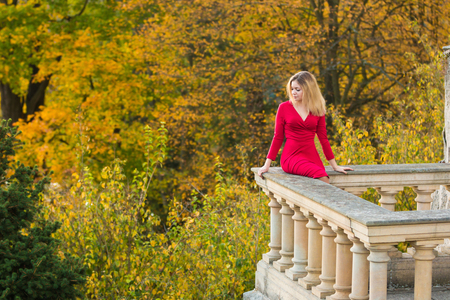 Beautiful Woman in red dress and old arhitecture on Fall Nature Background