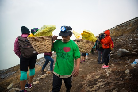 IJEN, INDONESIA - 11.11.2017: Sulfur miner carrying sulfur-laden baskets at Kawah Ijen volcano in Java, Indonesia.