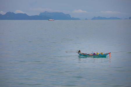 Fishermans in fishing boat in the blue sea