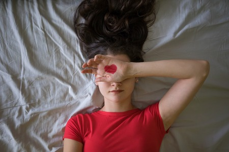 Attractive brunette young woman with drawing red heart on hands in the bed