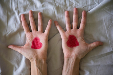 Drawing heart on hands of young woman on grey background Foto de archivo