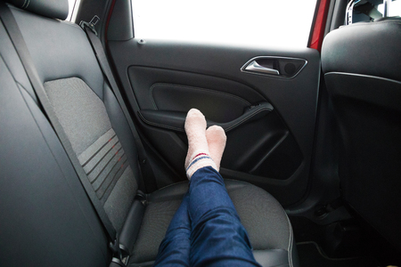 Womans legs in socks on car backseat during driving