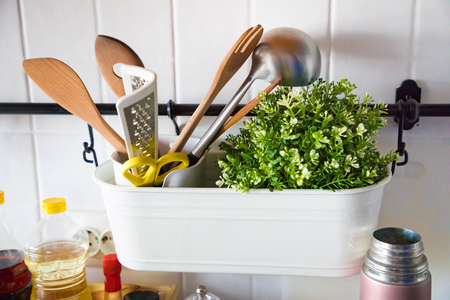 Kitchen set with wooden spoons, grater and green plant