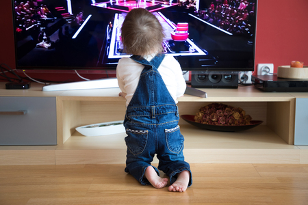 Baby boy watching TV at home Stockfoto