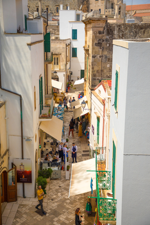 Otranto, Italy - 6.05.2018: People on Narrow streets of the old town in Otranto, Small typical alleys, Italy