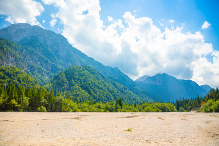 Parched bottom of Lake Predil with turquoise water and mountains in background near Tarvisio in European Alps in Italy Foto de archivo