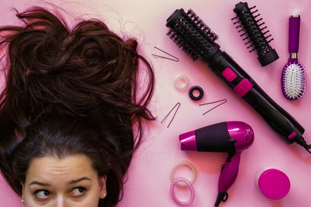 Portrait of brunette smiling and professional hairdressing tools on pink background