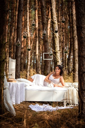 Woman with rabbit in bed in the morning on the nature background of deep forest Foto de archivo