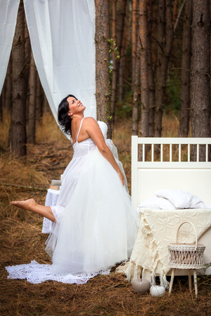 Woman is trying on wedding dress next to bed in the morning on the nature background of deep forest, morning of the bride concept Foto de archivo - 109137220