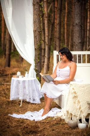 La mujer está leyendo el libro en la cama en la mañana en el fondo la naturaleza del bosque profundo Foto de archivo - 109137285