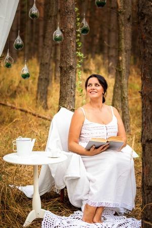 La mujer está leyendo el libro en la mañana en el fondo de la naturaleza del bosque profundo Foto de archivo - 109137299