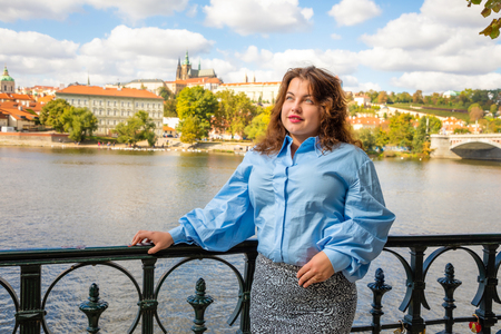 Portrait of young woman Old Town of Prague and river Vltava background in sunny september day, Czech Republic Foto de archivo - 109227628