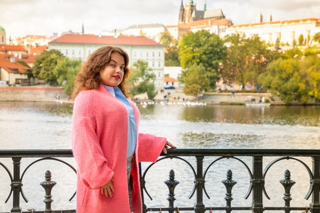 Portrait of young woman Old Town of Prague and river Vltava background in sunny september day, Czech Republic Foto de archivo - 109227630