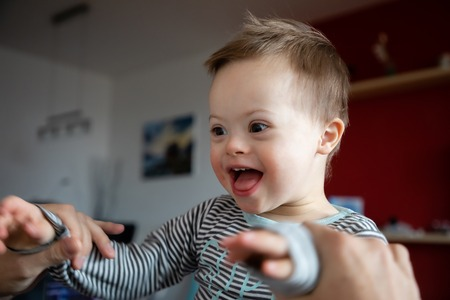 Cute boy with Down syndrome playing with dad on in home living room Foto de archivo - 109493052