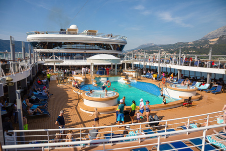 Mediterranean sea, Montenegro - 15.10.2018: Tourists relax at the swimming pool at Cruise liner Norwegian Star during a cruise to Greece