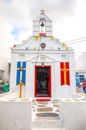 Mykonos, Greece - 17.10.2018: Agia Kyriaki Church, typical Greek church white building with red dome against the blue sky on the island Mykonos in Greece Redakční