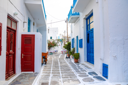 Traditional houses with blue doors and windows in the narrow streets of greek village in Mykonos in Greece 免版税图像