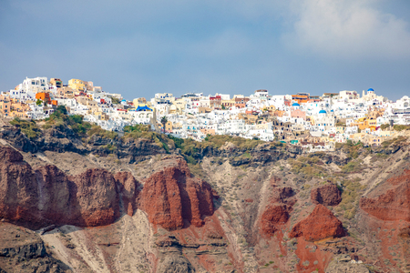 View of Oia village with white houses on red rocks caldera of Santorini Island in Greece
