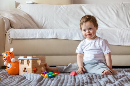 Piccolo ragazzo carino con sindrome di Down che gioca con un giocattolo nel soggiorno di casa