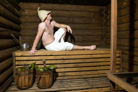 Man in a wooden Russian bathhouse and buckets with brooms Stok Fotoğraf