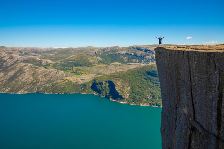 Hiker standing on Preikestolen and looking on the fjerd, Preikestolen - famous cliff at the Norwegian mountains, Norway