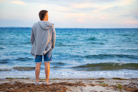 Young man on the beach of north sea in sunset time in Norway