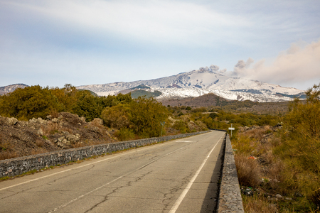 Road to volcano and snow covered Etna Mount, Sicily in Italy Stock Photo