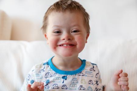Portret van schattige kleine jongen met het syndroom van Down thuis Stockfoto