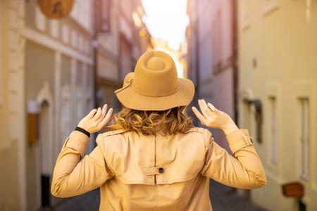 Girl in a beige hat and coat in narrow street of Prague city in Czech Republic Foto de archivo - 121430955
