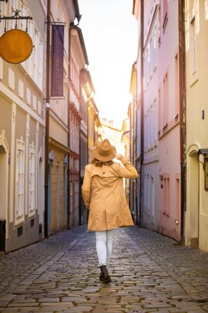 Girl in a beige hat and coat in narrow street of Prague city in Czech Republic Foto de archivo - 121430962