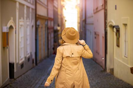 Girl in a beige hat and coat in narrow street of Prague city in Czech Republic Foto de archivo - 121431000