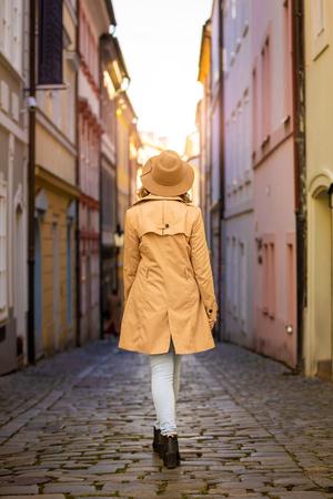 Girl in a beige hat and coat in narrow street of Prague city in Czech Republic Foto de archivo - 121431004