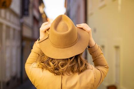 Girl in a beige hat and coat in narrow street of Prague city in Czech Republic Foto de archivo - 121435305