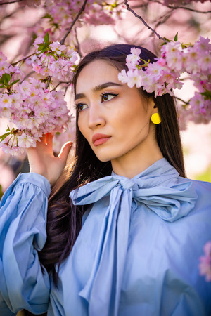 Beautiful young asian woman in blooming cherry blossoms garden in Prague Foto de archivo - 121435702