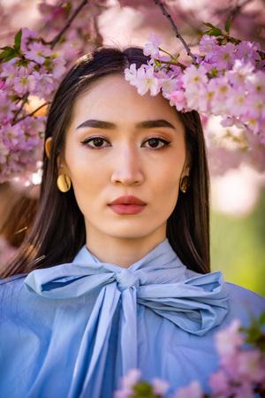 Beautiful young asian woman in blooming cherry blossoms garden in Prague Foto de archivo - 121435723