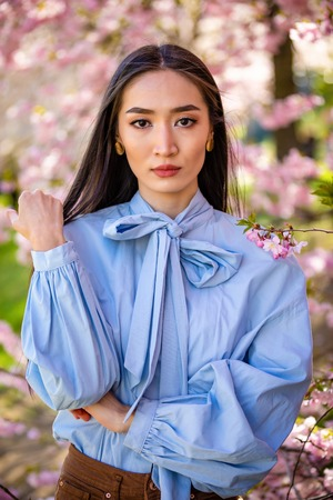 Beautiful young asian woman in blooming cherry blossoms garden in Prague Foto de archivo - 121435724