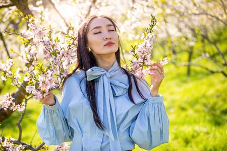 Beautiful young asian woman in blooming apple blossoms garden in Prague Foto de archivo - 121435847