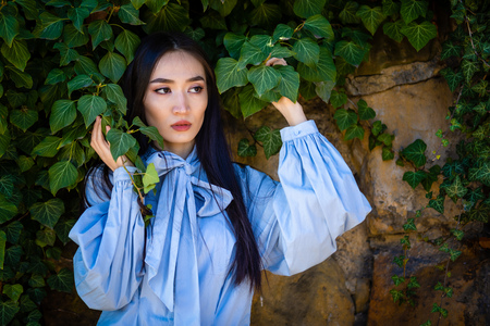 Portrait of young stylish asian woman in green leaves on stone wall background Foto de archivo - 121435848
