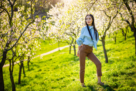 Beautiful young asian woman in blooming apple blossoms garden in Prague Foto de archivo - 121435852