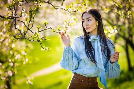 Beautiful young asian woman in blooming apple blossoms garden in Prague Foto de archivo - 121435854