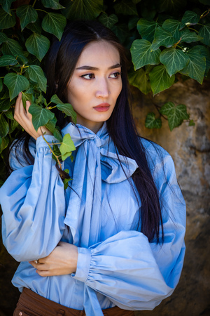 Portrait of young stylish asian woman in green leaves on stone wall background Foto de archivo - 121435856