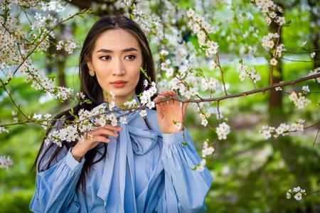 Beautiful young asian woman in blooming apple blossoms garden in Prague Foto de archivo - 121435857