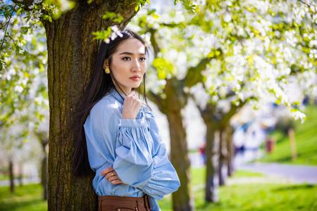 Beautiful young asian woman in blooming apple blossoms garden in Prague Foto de archivo - 121435858