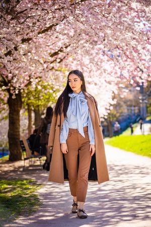 Beautiful young asian woman in blooming cherry blossoms garden in Prague Foto de archivo - 121435859