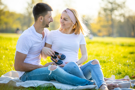 Happy couple expecting baby, pregnant young woman with husband sitting on green grass and holding baby blue boots, young family and new life concept Foto de archivo - 122019640