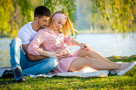 Happy couple expecting baby, pregnant young woman with husband, young family and new life concept Foto de archivo - 122019652