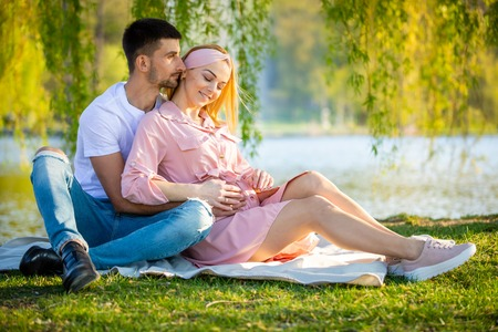 Happy couple expecting baby, pregnant young woman with husband, young family and new life concept Foto de archivo - 122020348