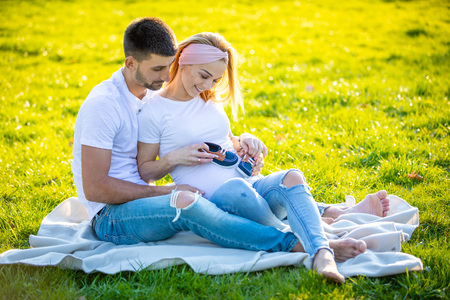 Happy couple expecting baby, pregnant young woman with husband sitting on green grass and holding baby blue boots, young family and new life concept Foto de archivo - 122020364